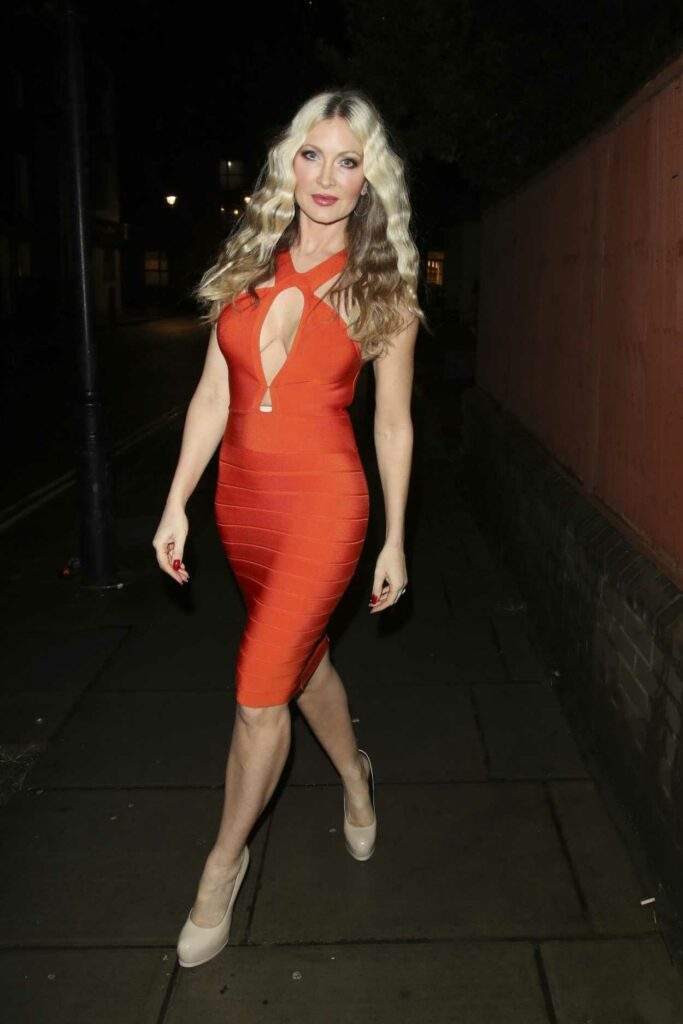 Caprice Bourret in an Orange Form Fitting Dress