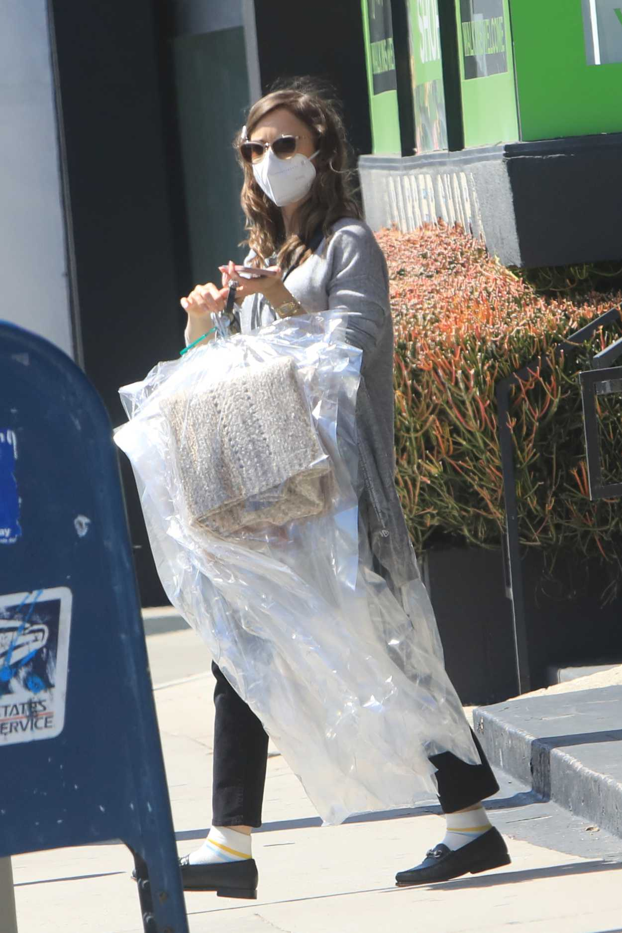 Lily Collins in a Grey Hoodie Picking up Clothing from the ...